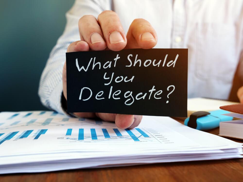 Man Holds Sign What Should You Delegate, Delegation Concept