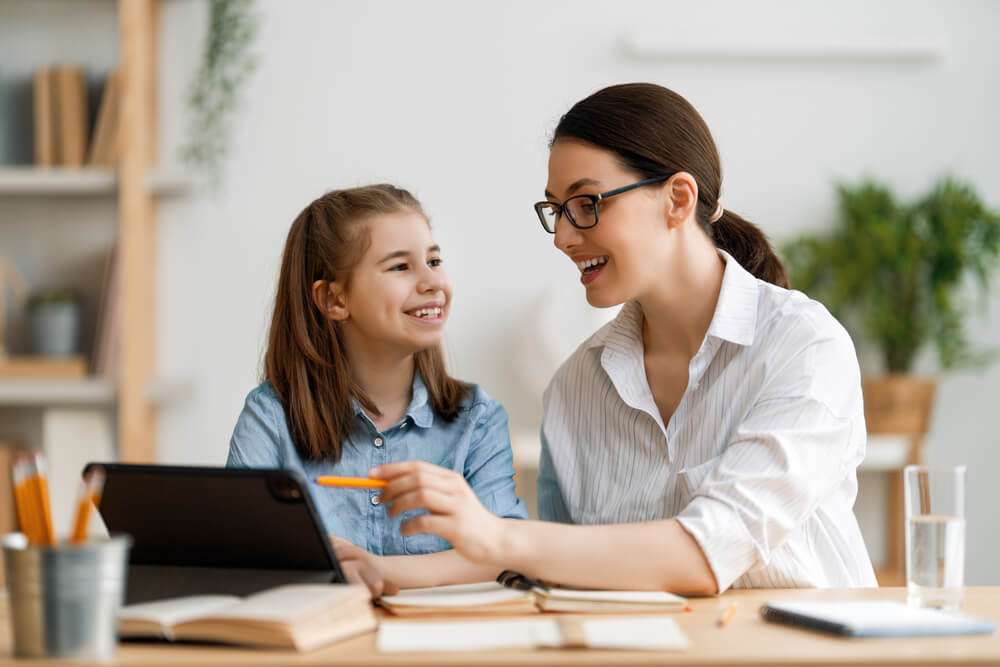 Happy Child and Adult Are Sitting at Desk. Girl Doing Homework or Online Education