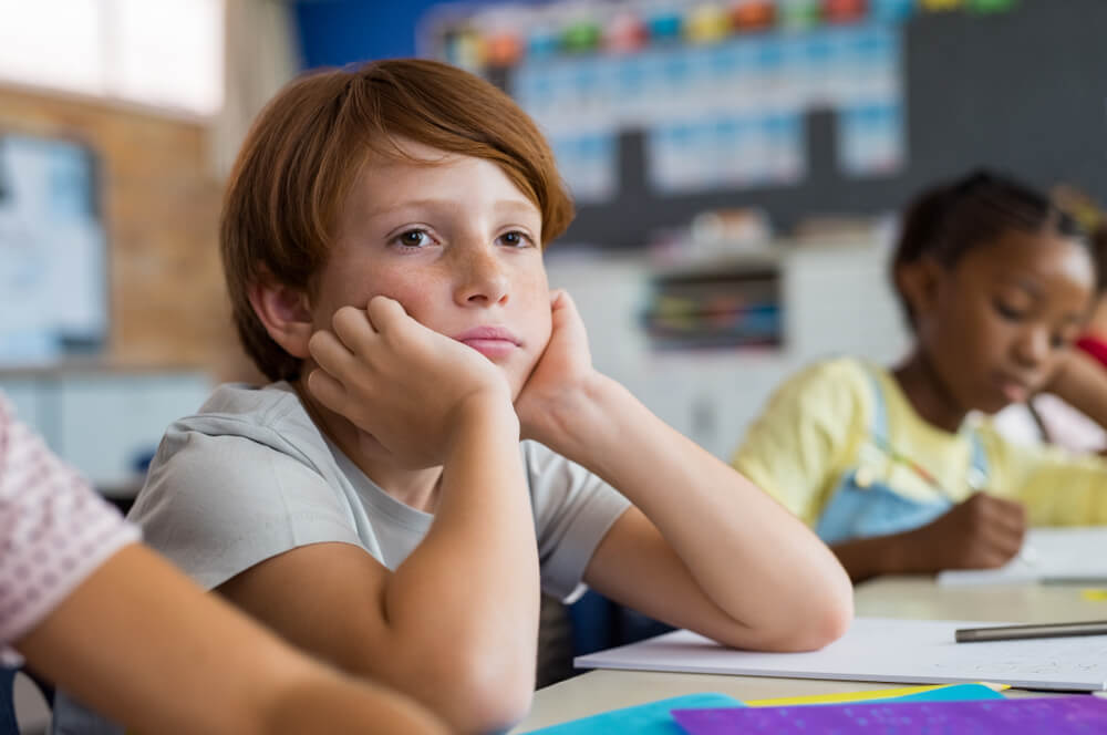 Tired School Boy With Hand on Face Sitting at Desk in Classroom